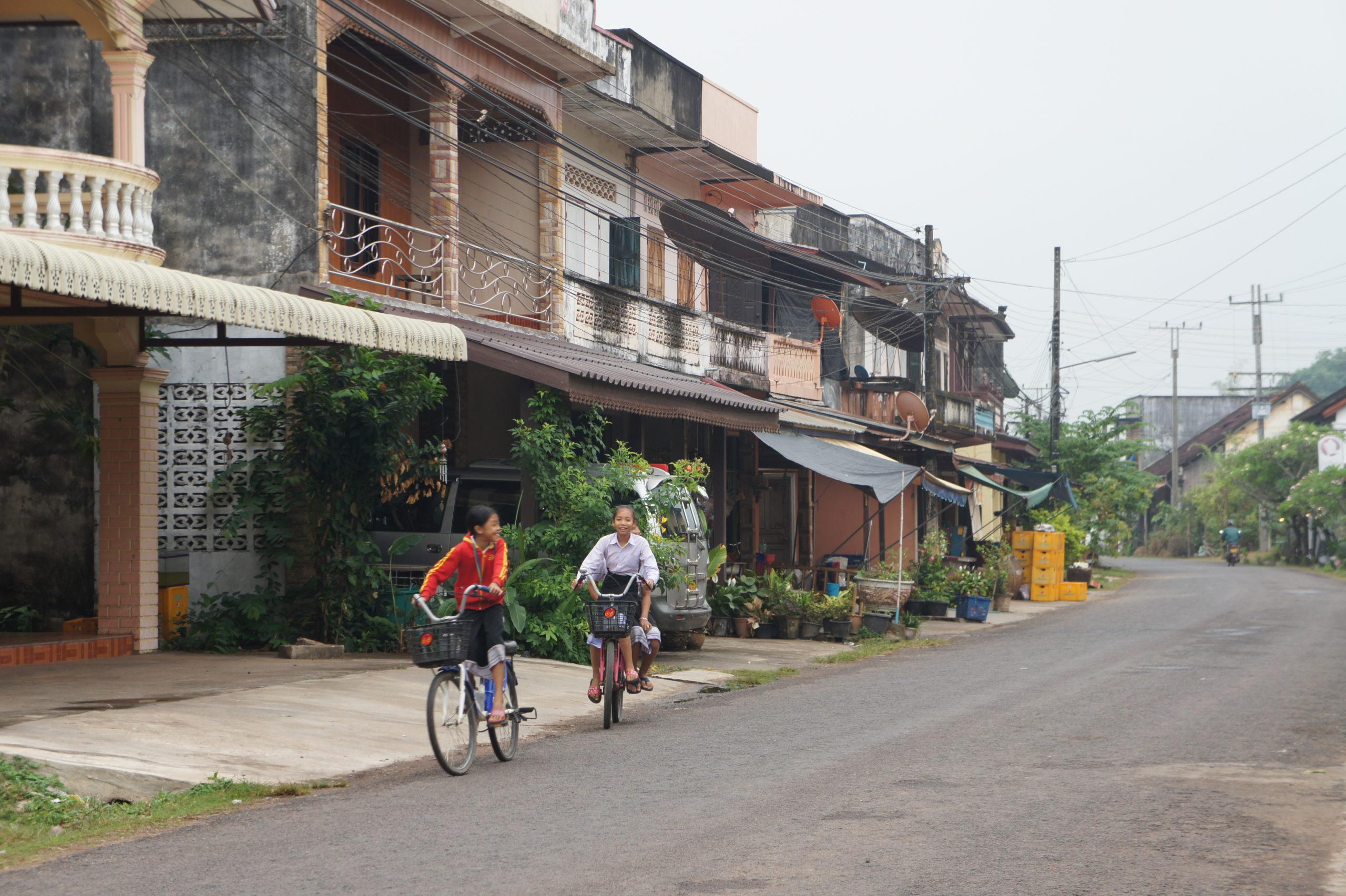 Deux enfants à vélo dans la rue principale de Champassak