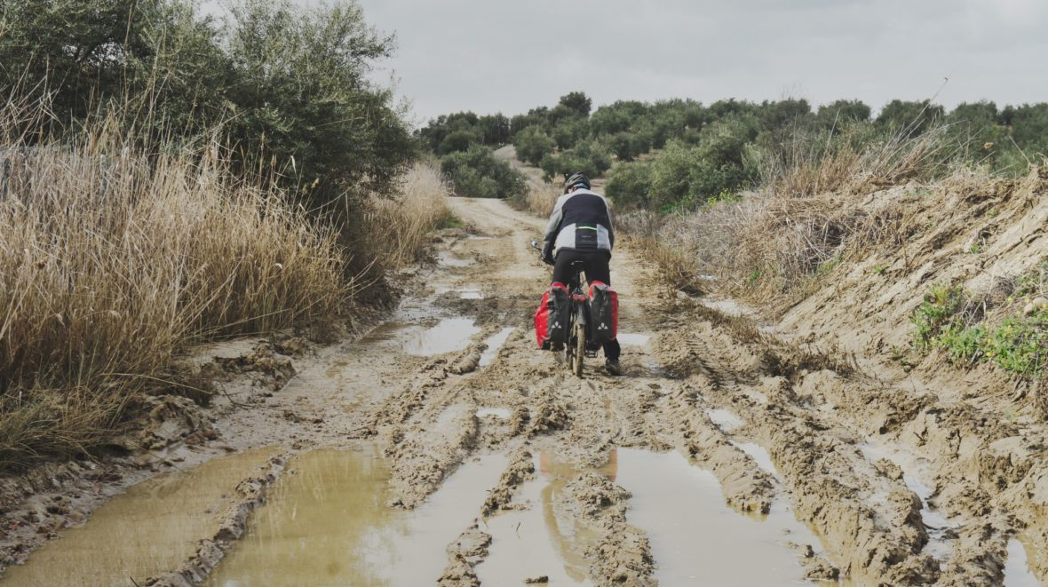 Jérôme à vélo sur un chemin très boueux d'Andalousie